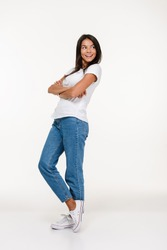 Full length portrait of a young smiling woman standing and looking away at copy space isolated over white background