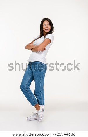 Full length portrait of a young smiling woman standing and looking away at copy space isolated over white background #725944636