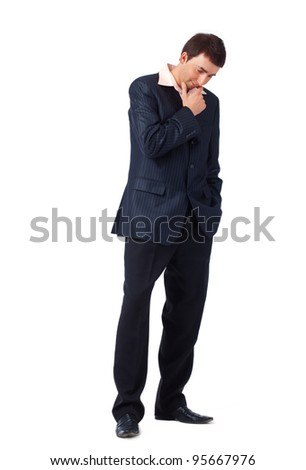 Full length portrait of a young thoughtful businessman, looking down.