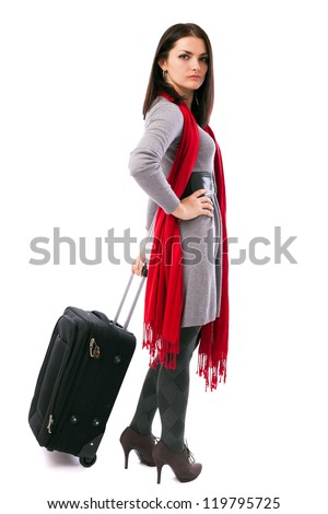Full length portrait of a young traveler woman holding a luggage isolated on white background