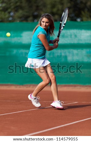 Full length portrait of a young woman playing tennis on a dross field