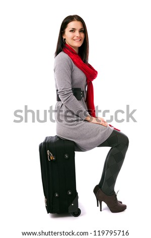 Full length portrait of a young woman sitting on luggage isolated on white background