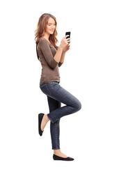 Full length portrait of a young woman typing a text message on her cell phone and leaning against a wall isolated on white background, studio shot