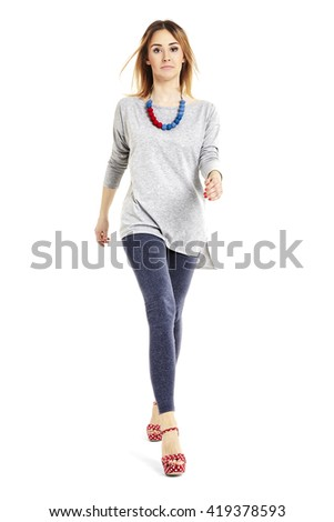 Full length portrait of a young woman walking and looking at you.  #419378593