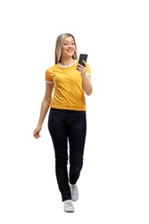 Full length portrait of a young woman walking and using a phone isolated on white background