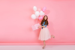 Full-length portrait of adorable birthday girl with curly hair wearing high heel shoes, holding present in cute box. Graceful slim young woman received gift with colorful helium balloons on holiday