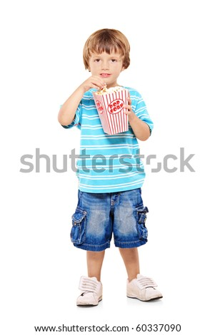 Full length portrait of adorable young boy eating popcorn isolated against white background