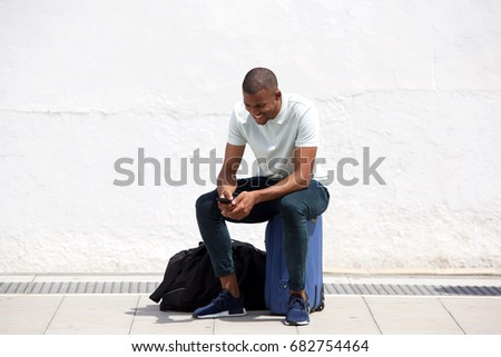 Full length portrait of african man sitting on suitcase and looking at mobile phone #682754464
