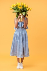 Full-length portrait of african woman in blue dress hiding behind the bouquet of flowers over yellow background