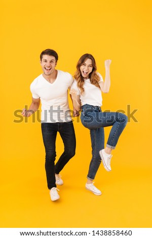 Full length portrait of amazed couple man and woman in basic t-shirts rejoicing while clenching fists isolated over yellow background