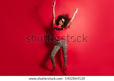 Full-length portrait of amazing black girl posing with hands up. Lovely african lady in sunglasses standing on red background.