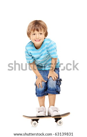 Full length portrait of an adorable young boy riding a skateboard isolated against white background