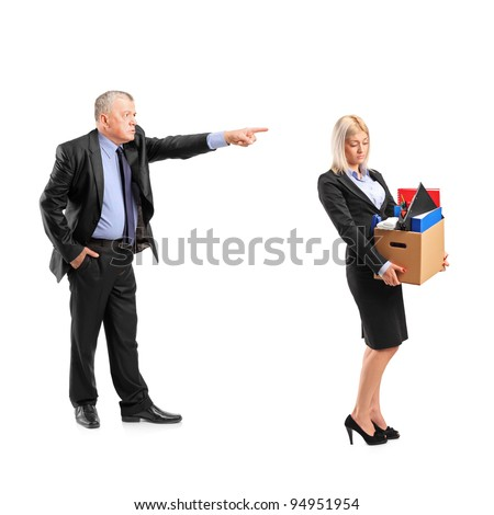 Full length portrait of an angry boss firing a woman in a suit carrying a box of personal items isolated on white background