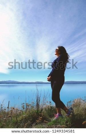 Full length portrait of an Asian woman in casual outfit and sunglasses standing on the lake shore having blue water and beautiful sky in the background. Image with copy space and vertical orientation. #1249334581