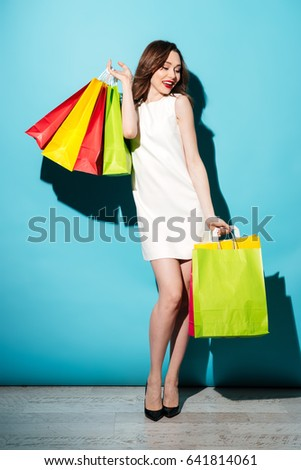 Full length portrait of an attractive cheerful woman holding colorful shopping bags and posing isolated over blue background