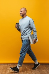 Full length portrait of an attractive happy confident casual young man walking over yellow background, carrying laptop computer, drinking takeaway coffee