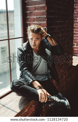 Full length portrait of an attractive man with fair hair wearing stylish leather jacket and jeans sitting on a window sill on a brick wall background on a sunny day, looking at camera.Texture effect. #1128134720