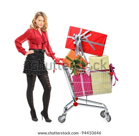 Full length portrait of an attractive woman pushing a shopping cart full of gifts isolated on white background
