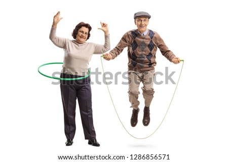 Full length portrait of an elderly woman with a hula hoop and a senior man jumping with a skipping rope isolated on white background