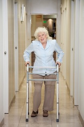 Full length portrait of an elderly woman with walker standing in hospital corridor