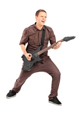 Full length portrait of an energetic young man playing on electric guitar, isolated on white background