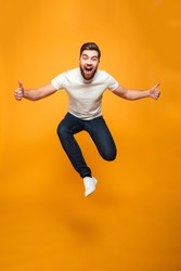 Full length portrait of an excited bearded man jumping and showing thumbs up isolated over yellow background