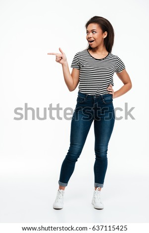 Full length portrait of an excited casual afro american woman pointing finger away isolated over white background #637115425