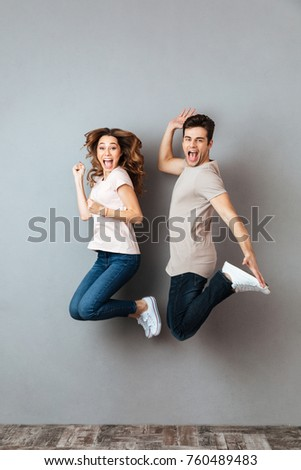Full length portrait of an excited couple jumping and looking at camera over gray wall #760489483