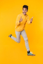 Full length portrait of an excited young african teenager boy jumping isolated over yellow background, showing thumbs up