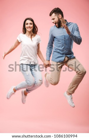 Full length portrait of an excited young couple holding hands while jumping isolated over pink background #1086100994