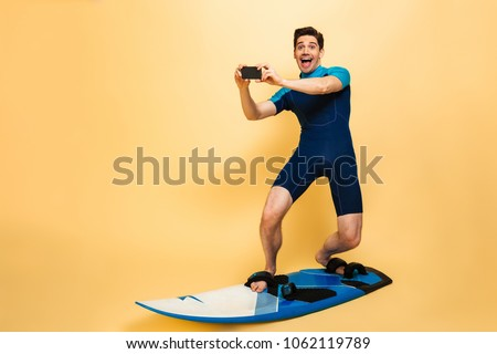 Full length portrait of an excited young man dressed in swimsuit talking a picture with mobile phone while surfing on a board isolated over yellow background