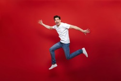 Full length portrait of an excited young man in white t-shirt jumping while celebrating success isolated over red background