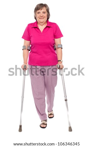 Full length portrait of an injured senior woman isolated over white background