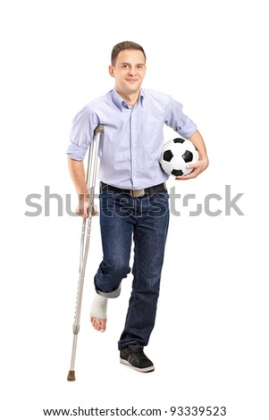 Full length portrait of an injured young man on crutches holding a football isolated on white background - stock photo