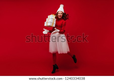 Full-length portrait of appealing ginger woman dancing at christmas party with gift. Indoor shot of adorable girl in white skirt having fun in new year.