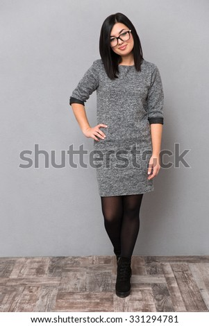 Full length portrait of attractive woman in dress and glasses standing on gray background. Looking at camera #331294781