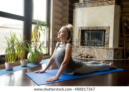 Full length portrait of attractive young woman working out at home in living room, doing yoga or pilates exercise on blue mat, pose for flexible spine