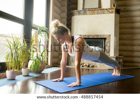 Full length portrait of attractive young woman working out for Living room yoga sessions