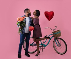 Full length portrait of beautiful black couple with roses, Valentine's gift and bike kissing on pink studio background. Affectionate African American woman and her boyfriend going for ride together