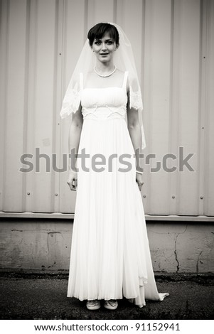 Full Length portrait of beautiful bride standing against wall