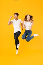 Full length portrait of beautiful couple man and woman in basic t-shirts rejoicing while clenching fists isolated over yellow background