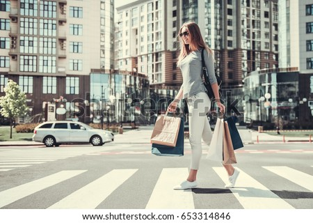 Full length portrait of beautiful girl in sun glasses holding shopping bags and smiling while crossing the road