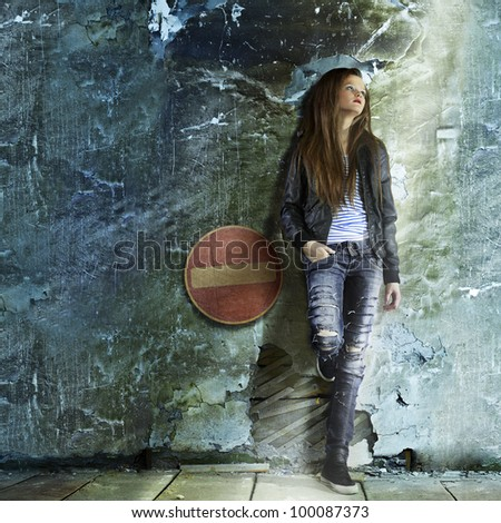 full-length portrait of beautiful glam rock style blonde girl standing near wall - stock photo