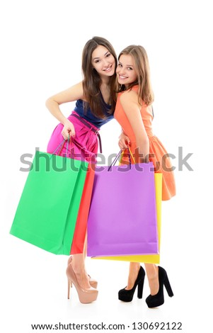 full length portrait of beautiful happy teen girls with colored shopping sale bags over white