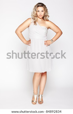 full-length portrait of beautiful plus size curly young blond woman posing on gray in white dress and court shoes