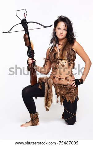 full-length portrait of beautiful woman fur hunter with crossbow on gray