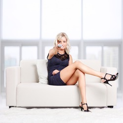 full-length portrait of beautiful young blond woman sitting on couch with remote control