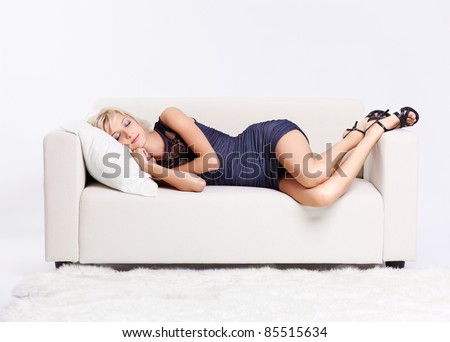 full-length portrait of beautiful young blond woman sleeping on couch with white furs on floor - stock photo