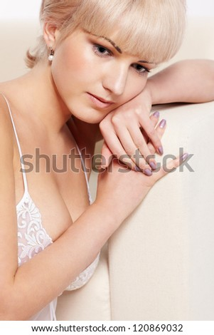 full-length portrait of beautiful young blonde woman in lingerie sitting near white coach