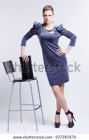 full-length portrait of beautiful young brunette business woman in stylish dress psoing aroubd  bar stool with clutch in hands